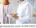 Stylish fashion designer working with measure red dummy as sketc 41001603