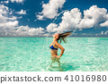 Woman splashing water with hair in the ocean 41016980