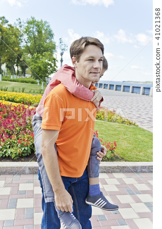 Son is hanging on father shoulders 41021368