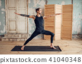 Male yoga doing stretching exercise on mat 41040348