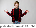 Cute confident serious little caucasian boy in checkered shirt meditating with closed eyes on grey 41046761