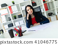 Beautiful young girl working with documents in the office. On the table are papers and a pencil. 41046775