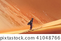 male hiker walking on sand desert 41048766