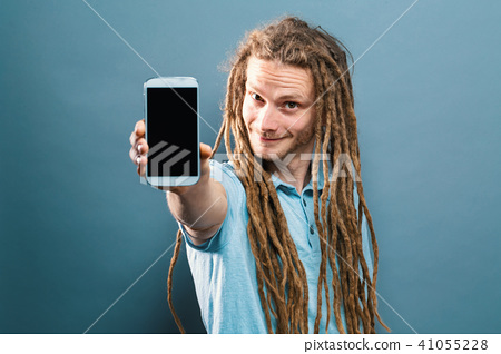 Young man holding out a cellphone 41055228