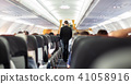 Interior of commercial airplane with steward walking the aisle. 41058916