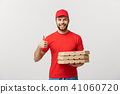 Pizza delivery concept. Young handsome delivery man showing pizza box and holding thumb up sign 41060720