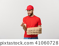 Delivery Concept: Handsome Pizza delivery man showing delicious expression over grey background 41060728