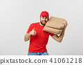 Pizza delivery concept. Young handsome delivery man showing pizza box and holding thumb up sign 41061218