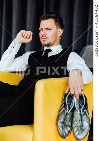 Stylish athletic man in a business costume vest holding a soccer ball. football player. 41064402