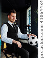 Stylish athletic man in a business suit and a soccer ball. Against the background of a loft wall. 41064434