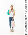 Full length portrait of a beautiful young woman posing with shopping bags, isolated on white 41066829