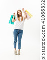 Full length portrait of a beautiful young woman posing with shopping bags, isolated on white 41066832
