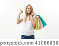 Smiling attractive woman holding shopping bags doing thumb up sign on white background with 41066838