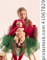 Happy little teen girl holding his newborn baby little sister. Family love. 41067829