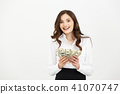Portrait of a cheerful young business woman holding money banknotes and celebrating isolated over 41070747
