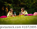 two little girl in dresses are playing at picnic 41072895