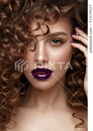 Beautiful girl with evening make-up, purple lips, curls and design manicure nails. beauty face. 41074027
