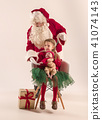 Christmas portrait of cute little newborn baby girl, dressed in christmas clothes, studio shot 41074143
