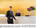 Hotel receptionist check in man giving key card 41076593