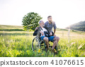 An adult hipster son with senior father in wheelchair on a walk in nature at sunset. 41076615