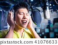 Asian male singer producing song in recording studio 41076633