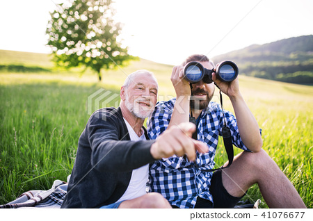 An adult hipster son with binoculars and senior father sitting on the grass in sunny nature. 41076677