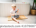 A toddler boy with a toothbrush sitting on the floor in the bathroom at home. 41076687