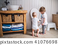 Two toddler children with toothbrush standing by the toilet in the bathroom at home. 41076698