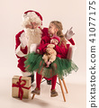 Christmas portrait of cute little newborn baby girl, dressed in christmas clothes, studio shot 41077175