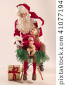 Christmas portrait of cute little newborn baby girl, dressed in christmas clothes, studio shot 41077194