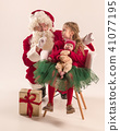 Christmas portrait of cute little newborn baby girl, dressed in christmas clothes, studio shot 41077195