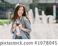 Asian backpack traveler girl using digital camera 41078045