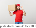 Cheerful young delivery man in red cap standing with parcel post box isolated over white background 41079103