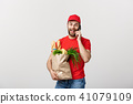 Handsome grocery delivery man talking to mobile and holding grocery paper bag. 41079109