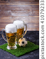 Photo of two beer mugs, green grass with soccer ball 41079233