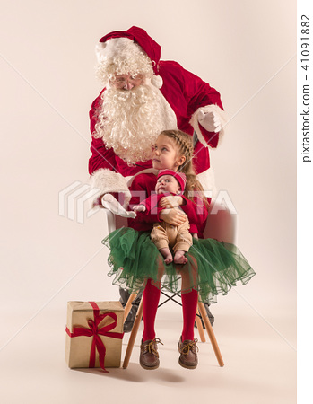 Christmas portrait of cute little newborn baby girl, dressed in christmas clothes, studio shot 41091882