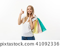 Smiling attractive woman holding shopping bags doing thumb up sign on white background with 41092336