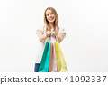 happy attractive caucasian woman offering shopping bags over white background 41092337