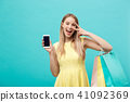 Portrait young attractive woman with shopping bags shows the phone's screen directly to the camera 41092369