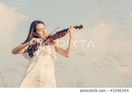 Beautiful Woman standing Playing the violin in 41096364