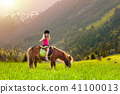 Kids riding pony. Child on horse in Alps mountains 41100013