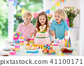 Kids birthday party. Children blow cake candles. 41100171