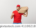 Pizza delivery concept. Young handsome delivery man showing pizza box and holding thumb up sign 41100218