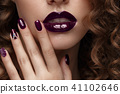 Beautiful girl with evening make-up, purple lips, curls and design manicure nails. beauty face. 41102646