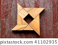 Tangram puzzle in shuriken shape on red old wood 41102935