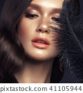 A beautiful girl with evening make-up, a Hollywood wave and a black feather in her hand. Beauty face 41105944