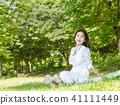 잔디밭에 앉아있는 젊은 여성모델 41111449