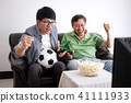 Young Asian Man and father watching soccer match on tv and cheer 41111933
