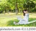 坐草坪和看膝上型計算機的一個年輕女性模型握一隻手 41112090