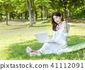 年輕女性模型坐草坪注視膝上型計算機 41112091